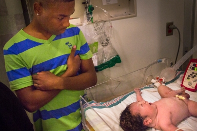 Dom, 16, looks on at his newborn son on July 22, 2014 at Unity Hospital in Rochester, NY.